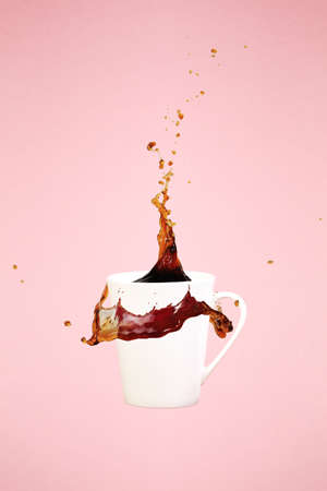 Coffee concept. Minimal art. Solid background. Coffee splashes. Levitating mug. Pink background. Vertical, straight cup