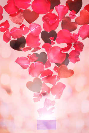 Rose petals and hearts flying out of a gift box. Pink background.  Valentine background. Romantic concept. Levitating flowers., bokeh effect Stock fotó