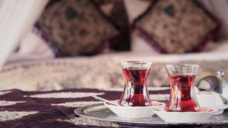 Two turkish tea cups and turkish delight with oriental canopy bed at the background. Silver tray. Romantic concept. Valentines background. Arabian nights ambiance. Horizontal, wide screen, cups on the right side, toned Stock Photo
