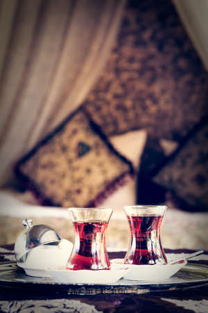 Two turkish tea cups and turkish delight with oriental canopy bed at the background. Silver tray. Romantic concept. Valentines background. Arabian nights ambiance. Vertical, toned Imagens