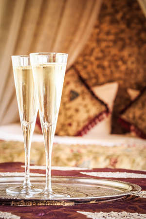 Two champagne glasses with oriental canopy bed at the background. Silver tray. Romantic concept. Valentines background. Arabian nights ambiance. Vertical, toned
