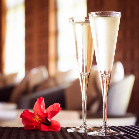 lounge: Two glasses of champagne with red flower in a spa lounge. Spa time concept. Spa lounge area. Valentines background. Romance concept. Square Stock Photo