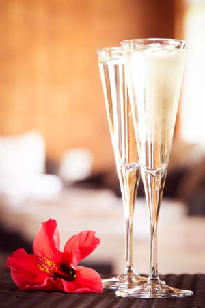 Two glasses of champagne with red flower in a spa lounge. Spa time concept. Spa lounge area. Valentines background. Romance concept. Vertical