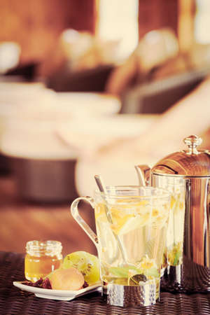 tea filter: Camomile tea with dried fruits. Woman at the background. Spa time concept. Spa lounge area. Vertical, tone filter
