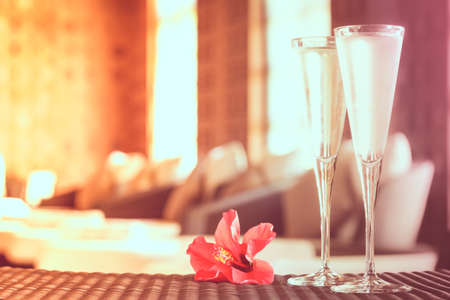 Two glasses of champagne with red flower in a spa lounge. Spa time concept. Spa lounge area. Valentines background. Romance concept. Horizontal, color filter applied