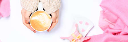 Female hands in beige knit holding cup of cappuccino. Gift alike dessert with heart shape sprinkles. Flat lay. Valentines concept. Pink textile. Horizontal, banner format