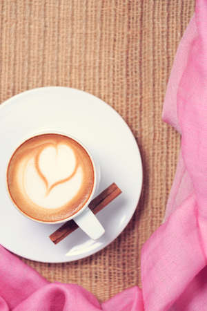 Coffee with pink scarf. Valentines concept. Rustic style. Flat lay view. Warm tone. Vertical Фото со стока