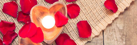 Enlightened candles in heart-shaped candleholders with red roses petals on rustic wooden background. St Valentines background. Romantic holiday concept. Top view. Horizontal, banner. Warm creamy tone Stock Photo