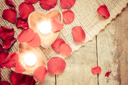 Enlightened candles in heart-shaped candleholders with red roses petals on rustic wooden background. St Valentines background. Romantic holiday concept. Top view. Horizontal. Warm light tone Stock Photo