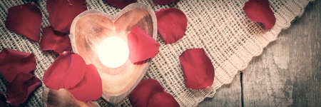 Enlightened candles in heart-shaped candleholders with red roses petals on rustic wooden background. St Valentines background. Romantic holiday concept. Top view. Horizontal, banner. Warm grunge tone