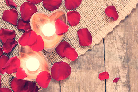 Enlightened candles in heart-shaped candleholders with red roses petals on rustic wooden background. St Valentines background. Romantic holiday concept. Top view. Horizontal. Warm creamy tone