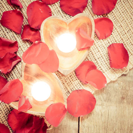 Enlightened candles in heart-shaped candleholders with red roses petals on rustic wooden background. St Valentines background. Romantic holiday concept. Top view. Square. Warm light tone