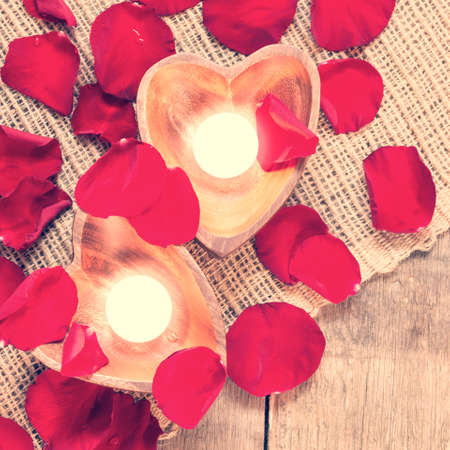 Enlightened candles in heart-shaped candleholders with red roses petals on rustic wooden background. St Valentines background. Romantic holiday concept. Top view. Square. Warm creamy tone