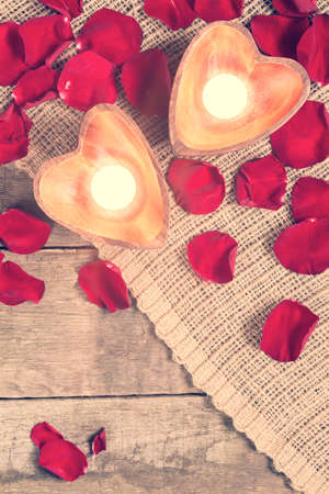 Enlightened candles in heart-shaped candleholders with red roses petals on rustic wooden background. St Valentines background. Romantic holiday concept. Top view. Vertical. Copy space at lower part. Warm creamy tone