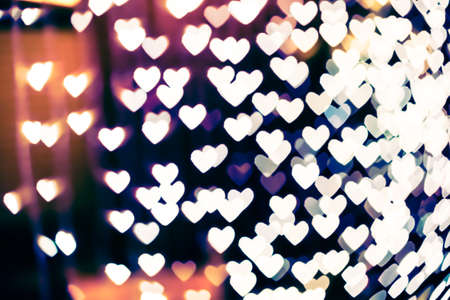 Heart shaped holiday blurred bokeh background. Valentine background. Christmas background. Horizontal.