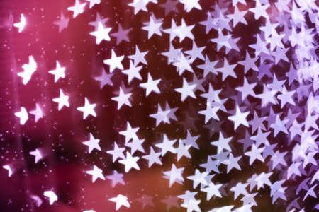 Star shaped holiday blurred bokeh background. Christmas background with sparkles. Celebration background. Horizontal.