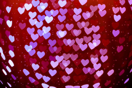 Heart shaped holiday blurred bokeh background with sparkles. Valentine background. Christmas background. Horizontal.