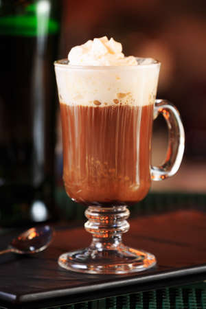 Irish coffee in a bar. Concept of St Patrick holiday. Holiday background. Irish national day. Warm tone. Vertical, close up
