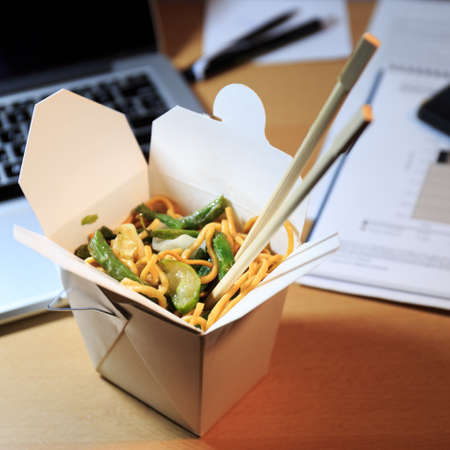 Chinese food box on the office desk. Eating at the office. Overtime work concept. Square