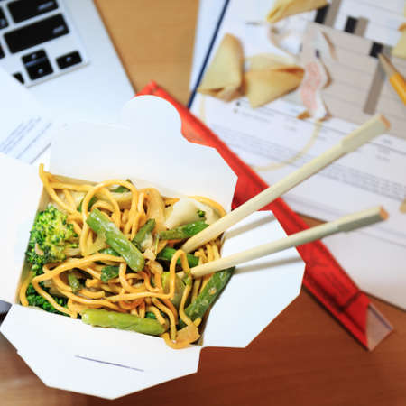Chinese food box on the office desk. Eating at the office. Overtime work concept. Top view. Square