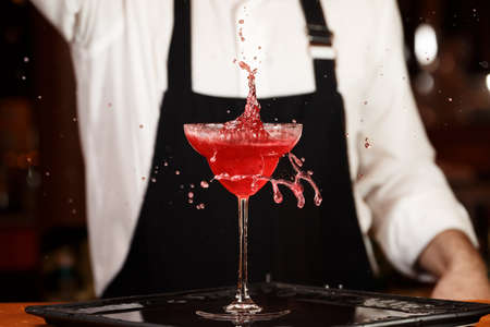 barmen: Barman in making cocktail at a nightclub. Nightlife concept. No face. Pouring into glass.. Horizontal