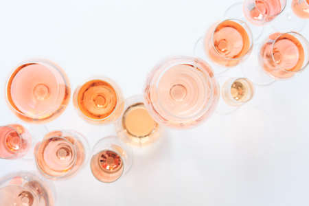 Many glasses of rose wine at wine tasting. Concept of rose wine and variety. White background. Top view, flat lay design. Natural light. Stock Photo