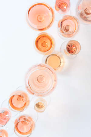 Many glasses of rose wine at wine tasting. Concept of rose wine and variety. White background. Top view, flat lay design. Natural light. Vertical Stock Photo