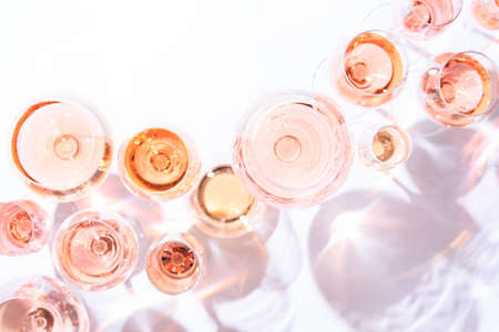 Many glasses of rose wine at wine tasting. Concept of rose wine and variety. White background. Top view, flat lay design. Direct sunlight. Toned image.