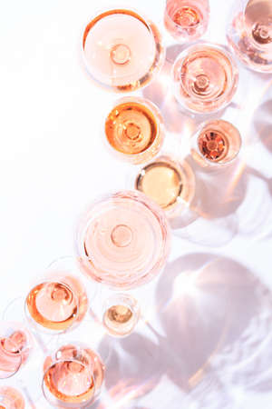 Many glasses of rose wine at wine tasting. Concept of rose wine and variety. White background. Top view, flat lay design. Direct sunlight. Toned image. Vertical