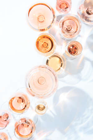 Many glasses of rose wine at wine tasting. Concept of rose wine and variety. White background. Top view, flat lay design. Direct sunlight. Vertical Stock Photo