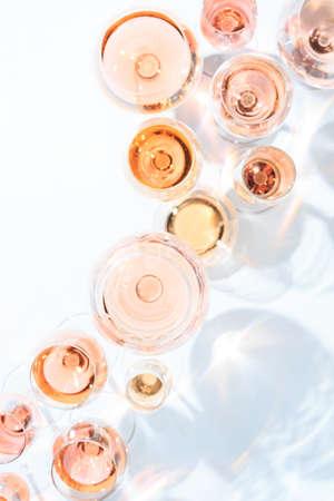 Viele Gläser Roséwein bei Weinprobe. Konzept des Roséweins und der Vielzahl. Weißer Hintergrund. Draufsicht, flaches Lay-Design. Direktes Sonnenlicht. Vertikal Standard-Bild - 75474981