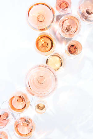 Muchos vasos de vino rosado en la degustación de vinos. Concepto de vino rosado y variedad. Fondo blanco. Vista superior, diseño plano lay. Vertical Foto de archivo - 75474977