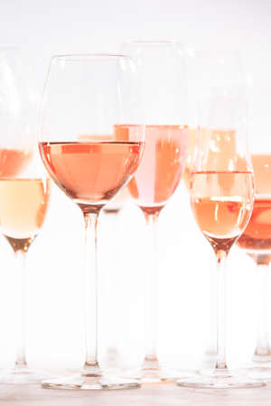 Many glasses of rose wine at wine tasting. Concept of rose wine and variety. White background. Vertical Stock Photo