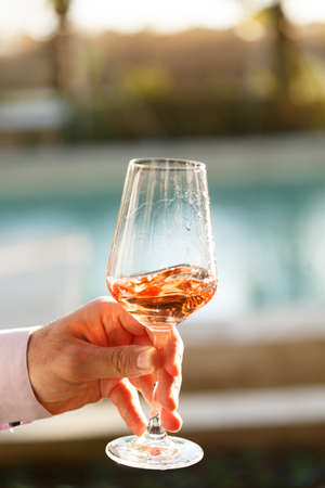 Swirling glass of rose wine at outdoor wine tasting. Concept of rose wine.  Vertical Stock Photo