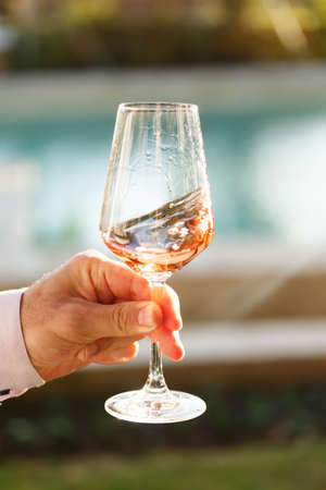 upscale: Swirling glass of rose wine at outdoor wine tasting. Concept of rose wine.  Vertical Stock Photo