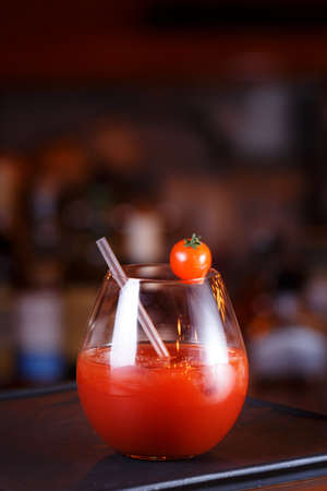 Bloody Mary or Ceasar cocktail at the bar counter. Classic cocktail. Dark background.  Vertical