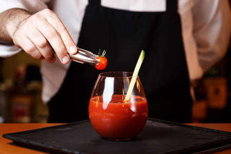 Bartender decorating Bloody Mary or Ceasar cocktail at the bar counter. Classic cocktail concept. Horizontal Stock Photo