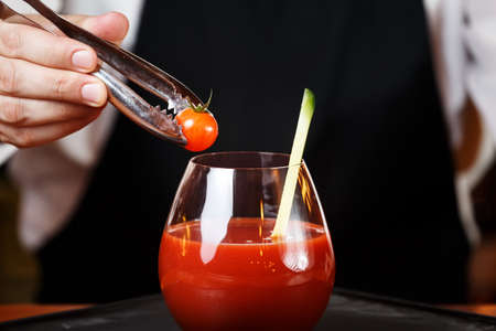 Bartender decorating Bloody Mary or Ceasar cocktail at the bar counter. Classic cocktail concept. Horizontal, close up Stock Photo