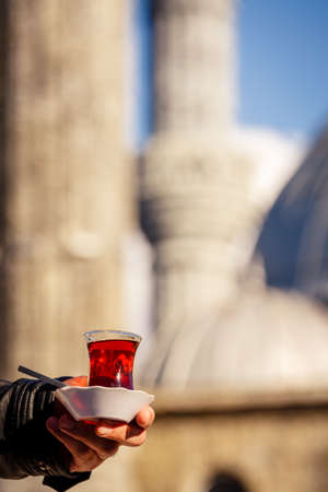 Male hand holding a cup of turkish tea. Hot turkish tea outdoors with a mosque at the background. Turkish tea and traditional turkish culture concept. Vertical. Toned image Stock Photo