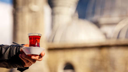 Male hand holding a cup of turkish tea. Hot turkish tea outdoors with a mosque at the background. Turkish tea and traditional turkish culture concept. Horizontal, wide screen format. Toned image