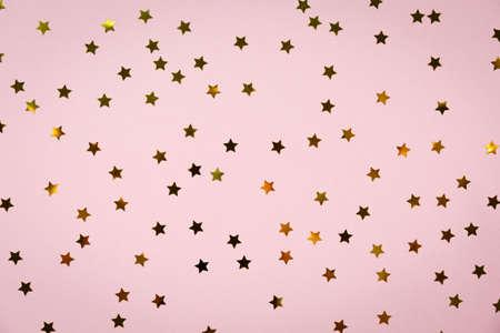 Estrela dourada polvilha em rosa. Fundo de feriado festivo. Conceito de celebração. Vista superior, lay plana. Horizontal Foto de archivo - 76443683