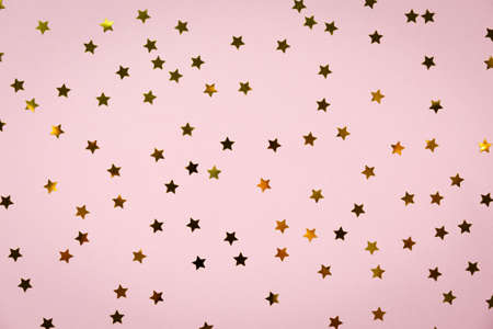 Golden star sprinkles on pink. Festive holiday background. Celebration concept. Top view, flat lay. Horizontal Imagens - 76443683