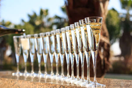 Many glasses of champagne or prosecco near resort pool in a luxury hotel. Pool party. Pouring drink into glasses. Horizontal