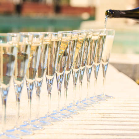 Many glasses of champagne or prosecco near resort pool in a luxury hotel. Pool party. Pouring drink into glasses. Square Stock Photo