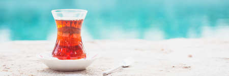 Hot turkish tea outdoors near water. Turkish tea and traditional turkish culture concept. Horizontal, banner format. Toned image