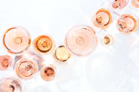 Many glasses of rose wine at wine tasting. Concept of rose wine and variety. White background. Top view, flat lay design. Horizontal