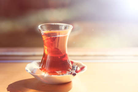 Hot turkish tea outdoors near glass wall. Turkish tea and traditional turkish culture concept. Horizontal. Toned image, warm sunset light and direct sunlight