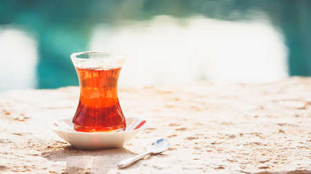 Hot turkish tea outdoors near water. Turkish tea and traditional turkish culture concept. Horizontal, wide screen format. Toned image Stock Photo