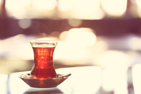 Hot turkish tea outdoors near glass wall. Turkish tea and traditional turkish culture concept. Horizontal. Toned image, warm sunset light