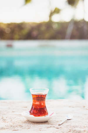 Hot turkish tea outdoors near water. Turkish tea and traditional turkish culture concept. Vertical. Toned image Stock Photo